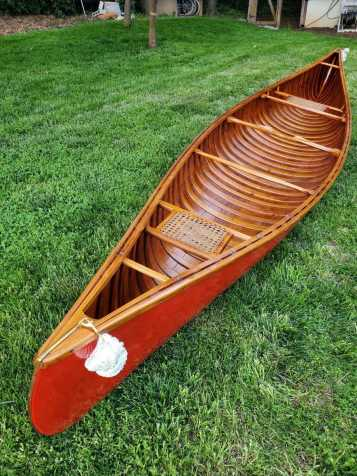 A photo of the bright red Horace Strong canoe sitting on a bright green mowed lawn. Photo taken for documentation.