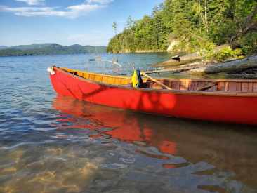 The bright red Horace Strong canoe in the foreground. The photo was taken on a sunny day at a lake, with an island and mountains in the background.