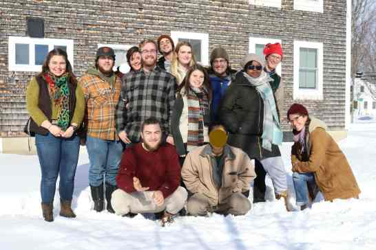 Sterling College student leaders stand smiling in the snow and sun, posing for a group picture outside the Madison House dorm. Some students are standing in the back, some are squatting in front. They are squinting and smiling in the sun.