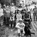 Black and White image of 12 people sitting and standing around tractor.