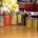 Multiples jars of canned goods in class jars on a wood countertop. Daffodils in background.