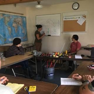 Azsa is standing in front of a whiteboard, teaching to a room of students.