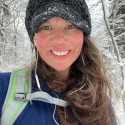 Christina is in the snowy woods hiking, wearing a blue hat and backpack