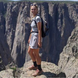 Abbey is wearing shorts and a tshirt and a backpack at the rim of a canyon