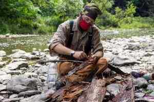 Ian is sitting streamside and stripping inner bark from cedar. He is wearing a bandana on his head and a COVID-19 face protection
