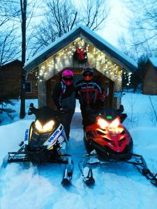 SNowmobiles in front of covered bridge at Sterling Ridge resort