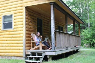 Girl on Sterling Ridge cabin front porch working from home