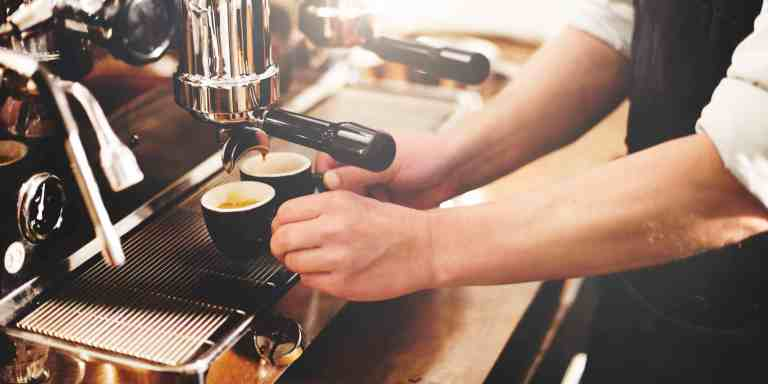 Barista an Kaffeemaschine