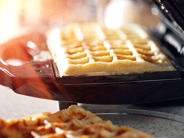 Freshly baked traditional Belgian waffles in iron waffle maker. family morning, prepare Breakfast