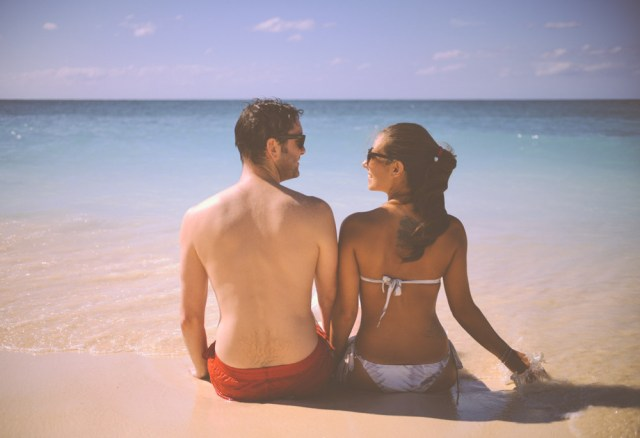 Cute-Man-And-Woman-Sitting-On-A-Beach-With-Sea