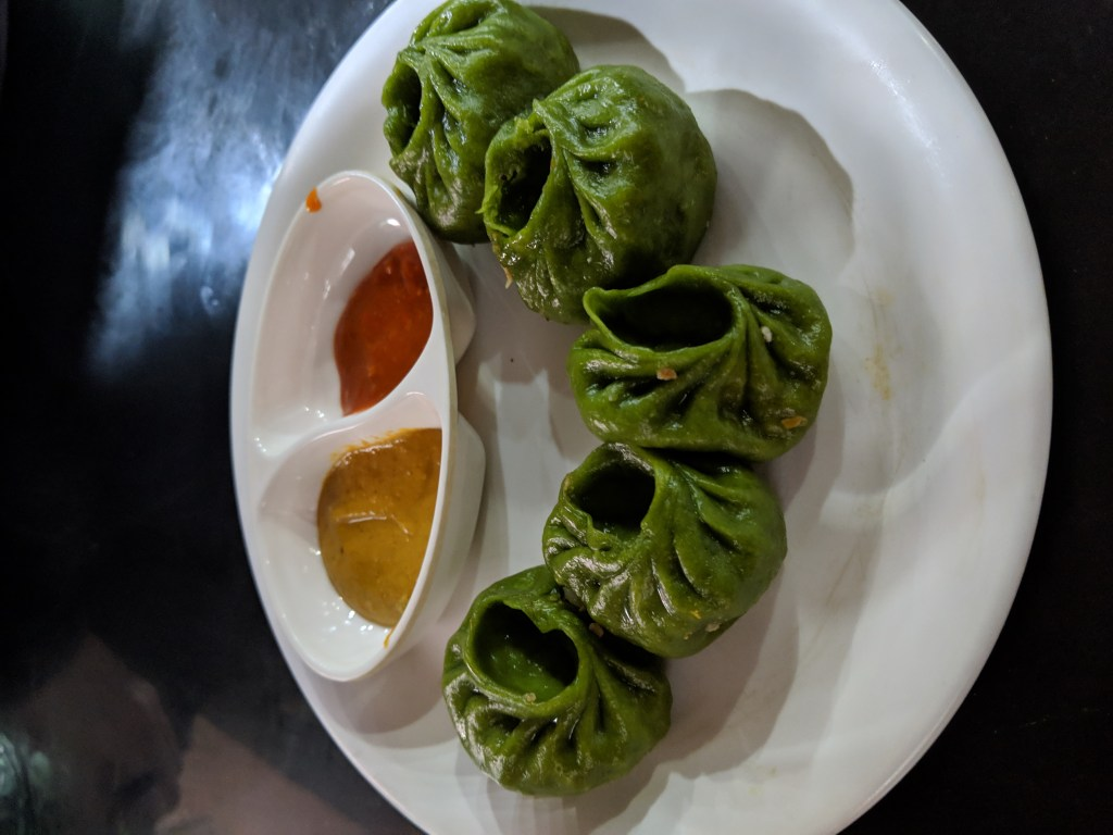 Spinach and cheese momos with spicy sauce and fried banana and chocolate dessert momos