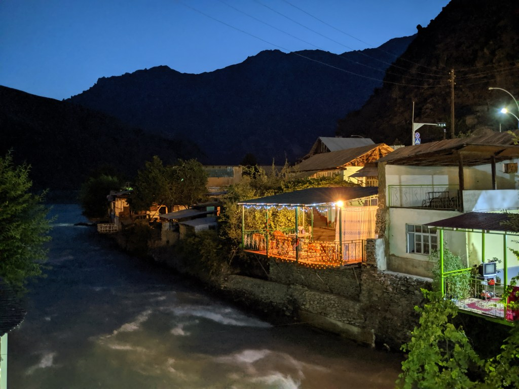 Patio lit up with a river and mountains in the background