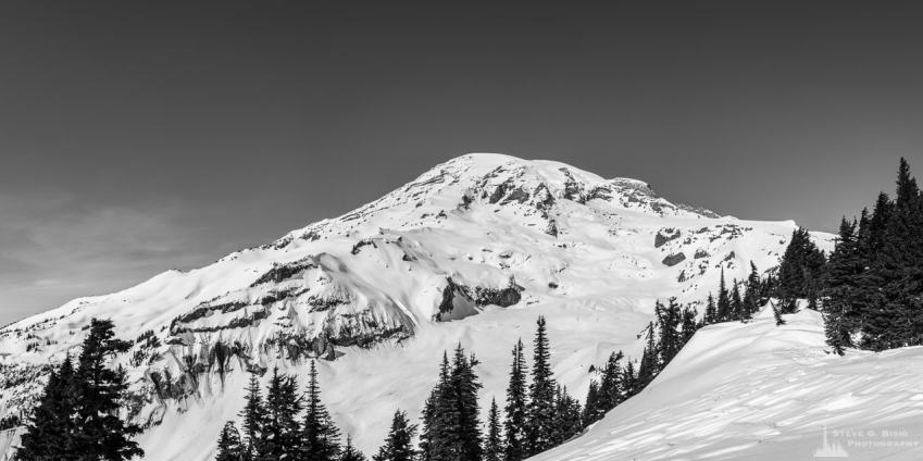 A black and white panoramic landscape photograph of Mount Rainier as viewed from the snow covered meadows near the Paradise Visiitors Center at Mount Rainier National Park, Washington.