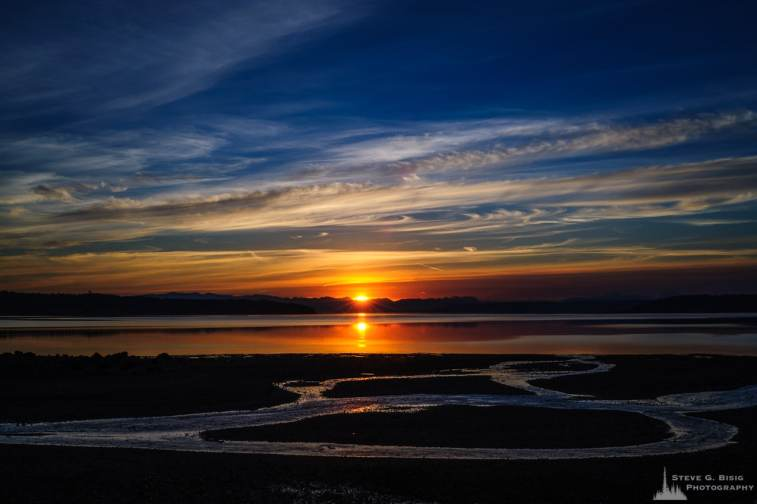 A landscape photograph of the August sunrise over Penn Cove on Whidbey Island near Coupeville, Washington.