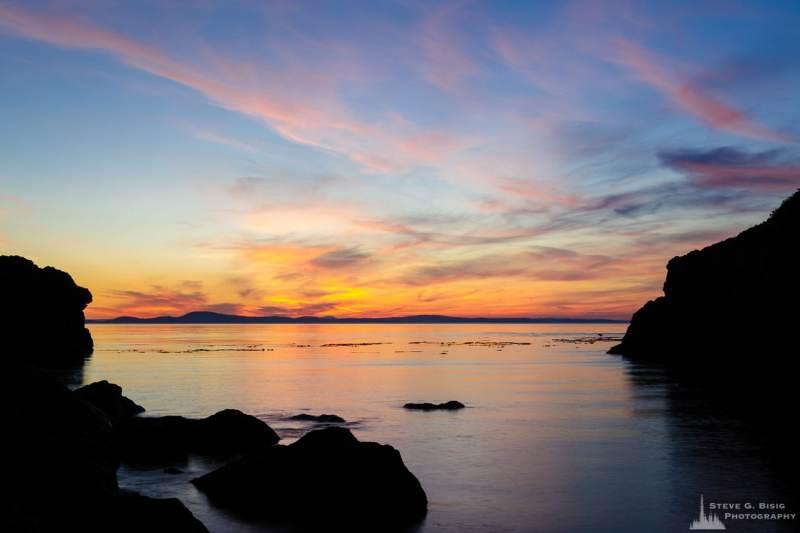 A landscape photograph of the setting sun along the rocky shoreline near Lighthouse Point at Deception Pass State Park, Washington.