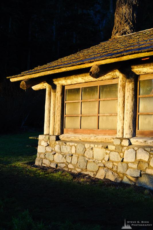 A Pacific Northwest photograph of the evening winter light shining on a historic shelter built by the Civilian Conservation Corps (CCC) along Bowman Bay at Deception Pass State Park, Washington.