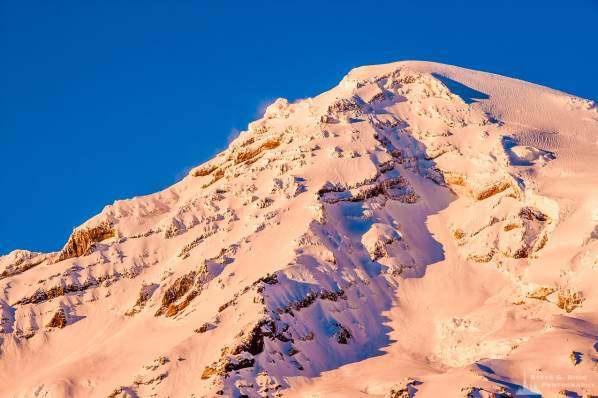 A closeup landscape photograph of the southwest corner face of a snow covered Mount Rainier on an early winter evening, captured along the Paradise Road at Mount Rainier National Park, Washington.