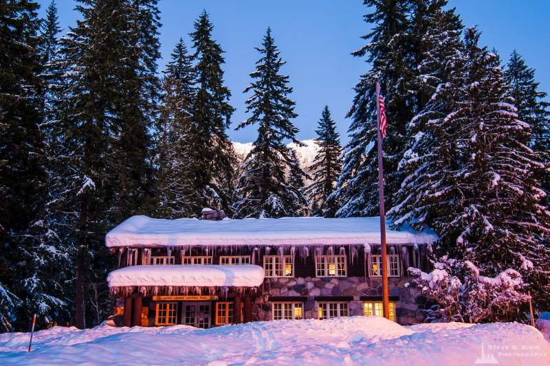 A photograph of the historic Administrative Building at dusk during the winter at Longmire, Mount Rainier National Park, Washington.