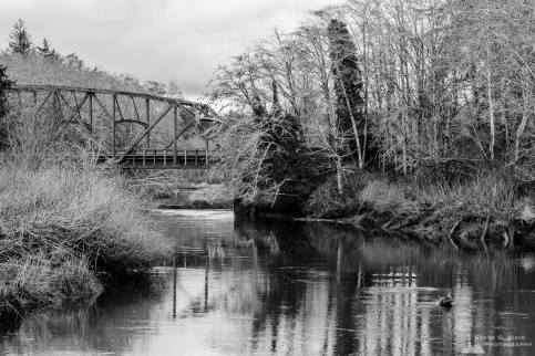 A black and white landscape photograph of the SR109 bridge over the Humptulips River in rural Grays Harbor County, Washington.