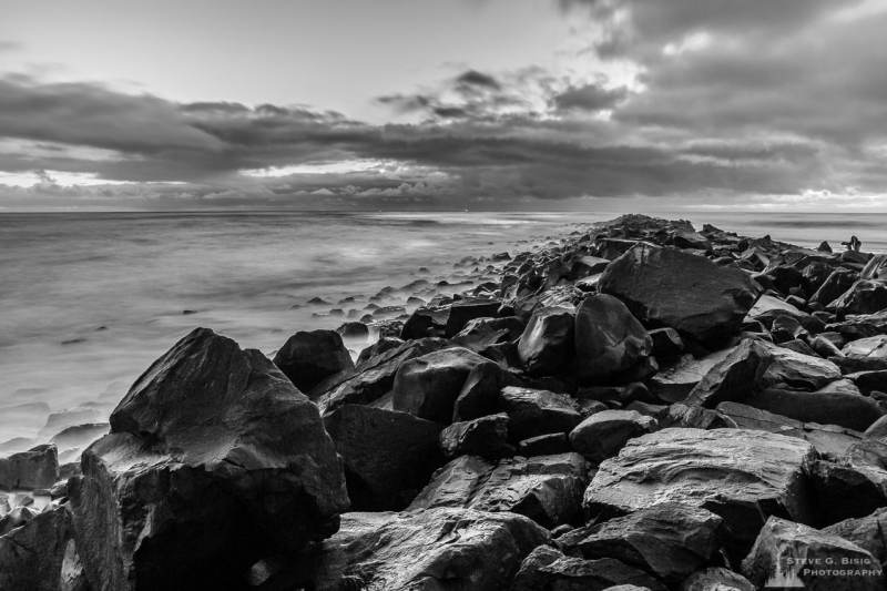 A black and white landscape photograph of the North Jetty of Grays Harbor at Ocean Shores, Washington on a cloudy winter night.
