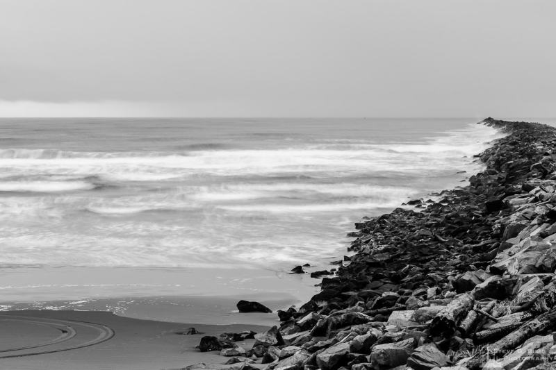 A black and white long exposure landscape photograph of the Pacific Ocean and beach along the South Jetty of Grays Harbor at Westhaven State Park near Westport, Washington.