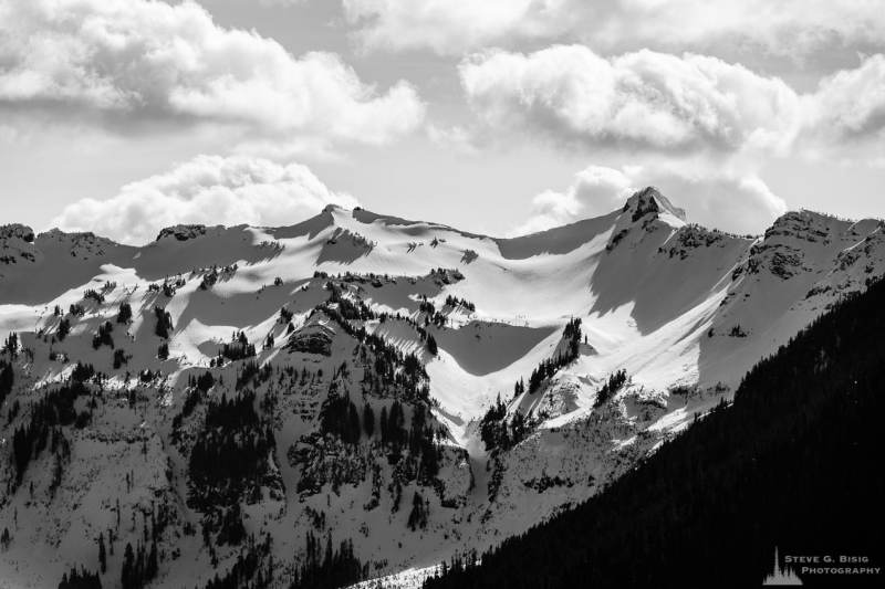 A black and white landscape photograph of the snow-covered Chimney Rock and surrounding mountain ranges in the Goat Rocks Wilderness Area as viewed from Gifford Pinchot National Forest Road 1284 in Lewis County, Washington.