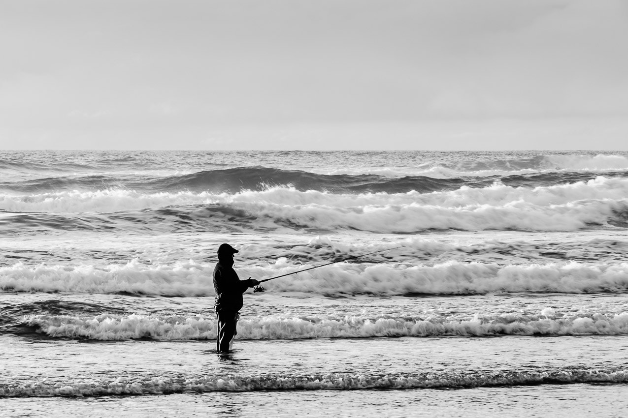 A black and white photograph of a fisherman fishing the Pacific Ocean surf at Tolovana Beach State Recreation Site near Cannon Beach, Oregon.