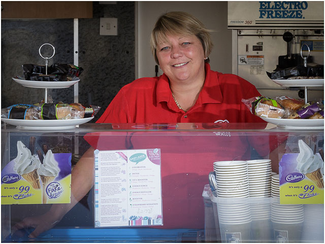 Portrait Of Charity Swimmer At The Counter Of Her Ice Cream Kiosk