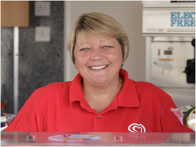 Portrait Of Ice Cream Kiosk Owner At Serving Counter Wearing Red Top
