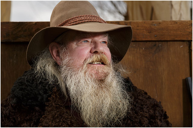 Head And Shoulders Portrait Of A Man Dressed As Wild West Trapper With A White Bushy Beard