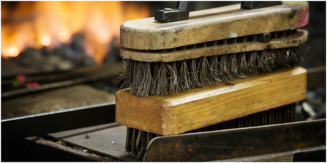 Blacksmiths Wire Brushes On Edge Of Forge