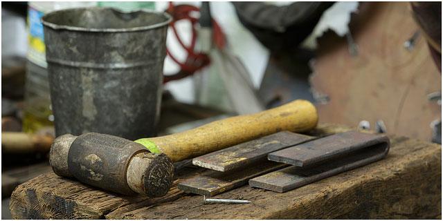 Hammer Laying On Wooden Block In Blacksmiths Workshop