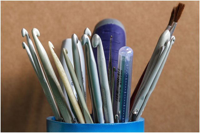 Collection Of Plastic Crochet Needles In Blue Plastic Cup