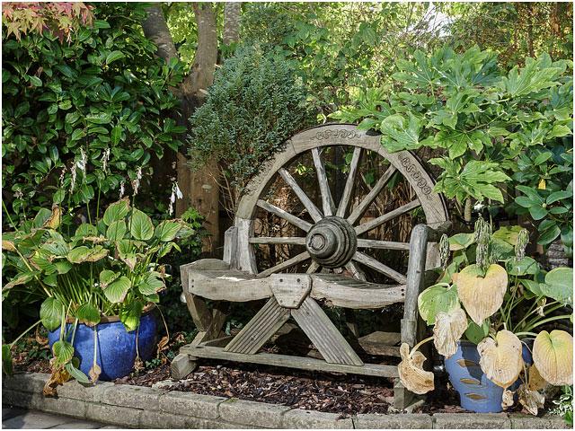 Wooden Wood Wagon Wheel Garden Seat Green Foliage Blue Pots