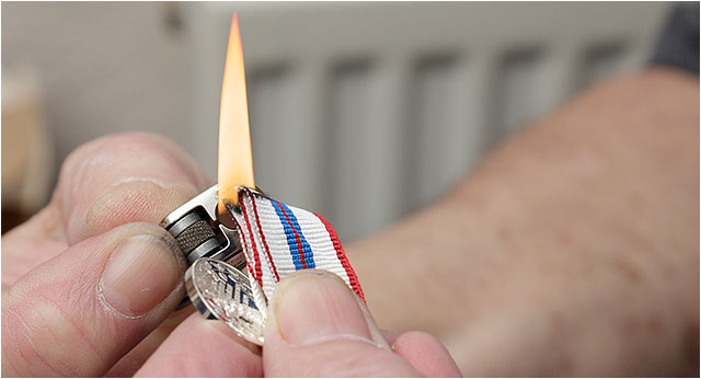 Sealing the edge of a medal ribbon with a lit cigarette lighter