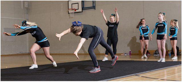 Cheerleaders practicising tumbles and flips