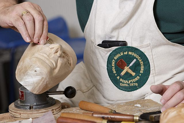 close up of woodcarver at work during a solent woodcarver and sculptors guild carve-in