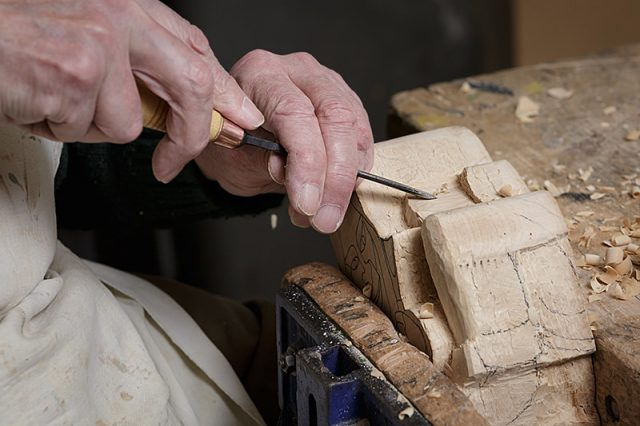 close up of woodcarvers hands working on a gargoyle carving