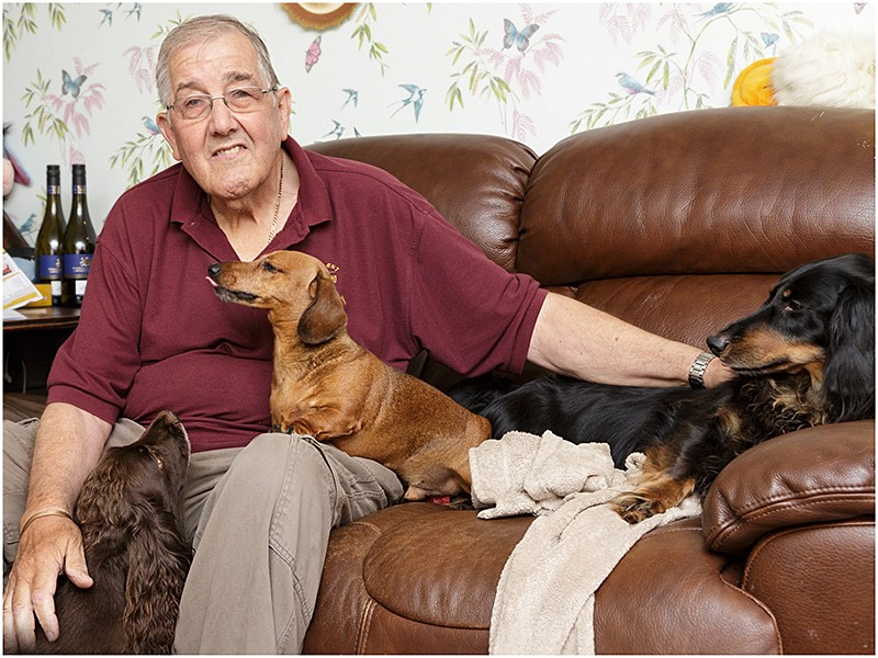 Meccano Enthusiast Seated With Pet Dogs On Sofa