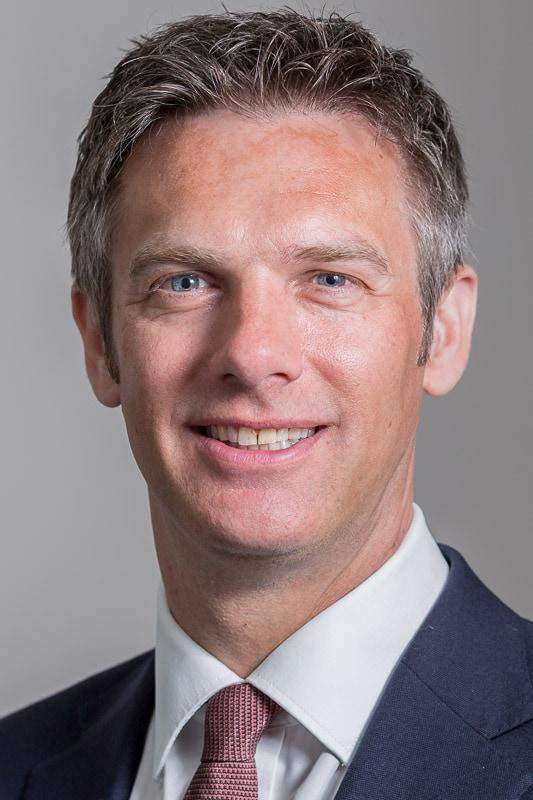 formal businessman headshot against mid grey background
