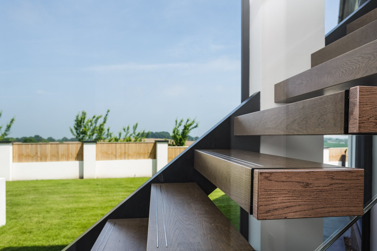 Feature staircase treads against glass wall with view to garden