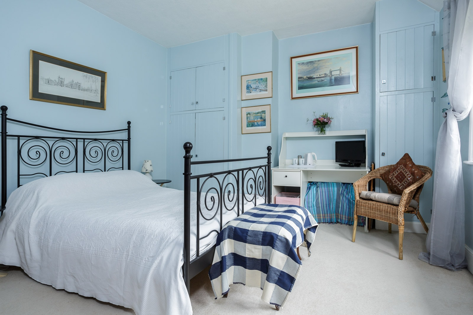 Country house bedroom with iron bed and predominantly blue colour scheme