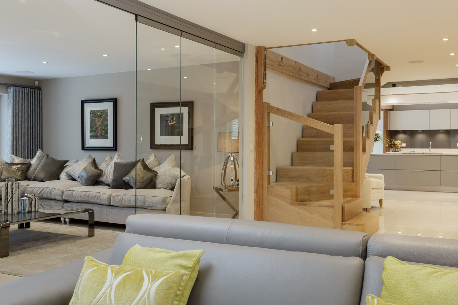 scene inside a modern luxury self build house with view of kitchen, lounge and wooden stairwell