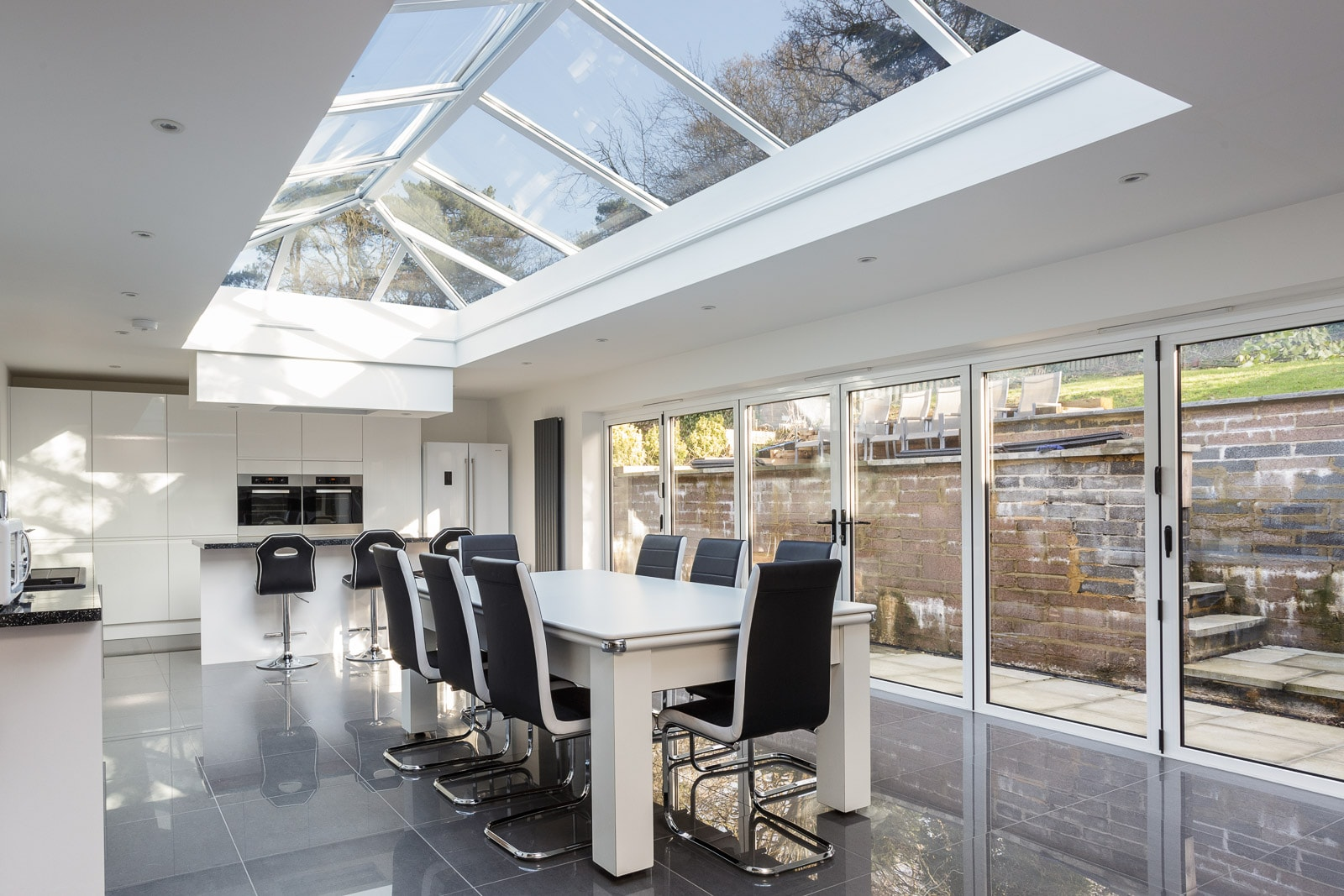 High specification modern kitchen or dining seating area with glass ceiling and walls