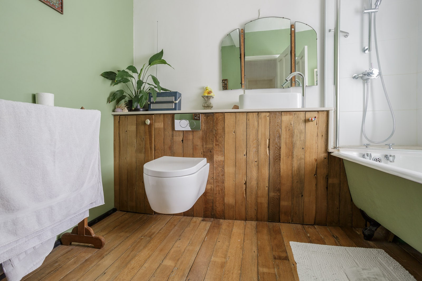 Rustic style bathroom with white porcelain toilet mounted on wooden panel with matching flooring