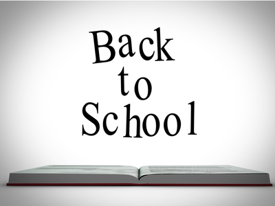 Back to school message above open book graphic on white background with vignette