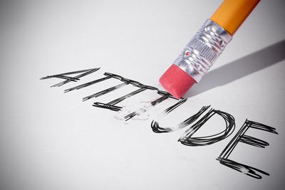 Pencil erasing the word attitude on paper