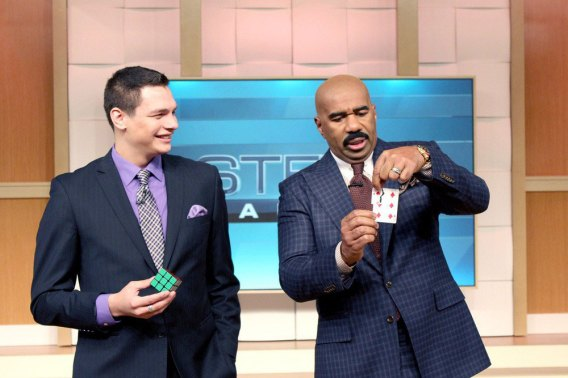 Magician Steven Brundage performs a card trick for Steve Harvey