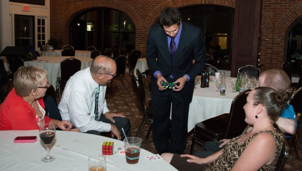 Audience watches in amazement as Magician Steven Brundage performs Rubik's Cube magic at a private event