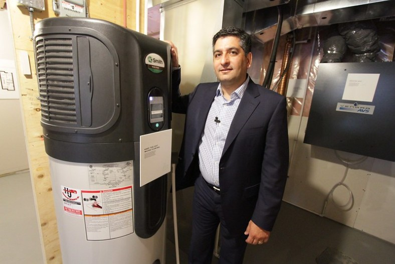 Photo of Bijan Mananni standing next to a hybrid electric water heater.